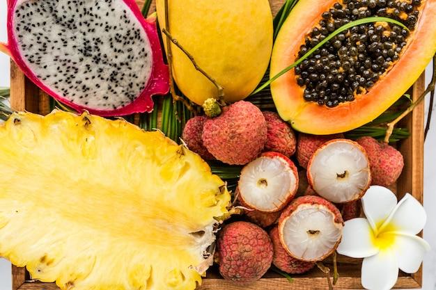 プルメリアの花と木製の箱のクローズアップで新鮮なエキゾチックなフルーツ Premium写真
