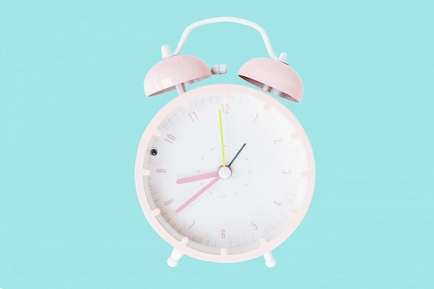 青色の背景に分離された目覚まし時計 Premium写真