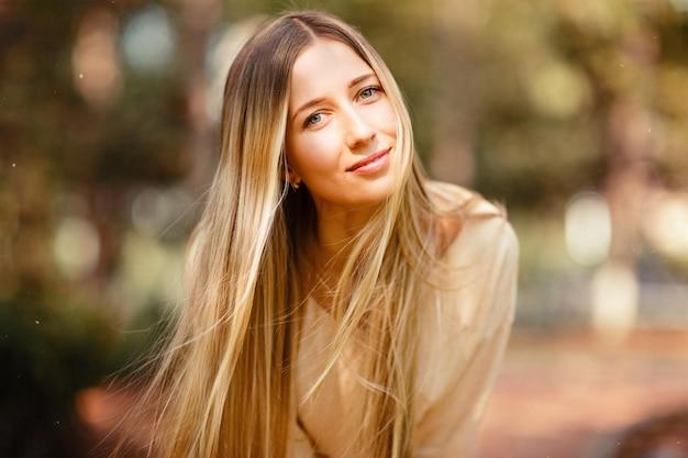Портрет красивой женщины с длинными светлыми волосами на открытом воздухе Premium Фотографии