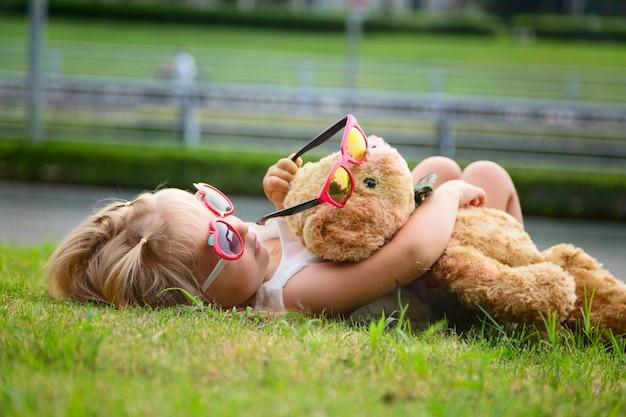 草の上に横たわるとテディベアを抱いて少女 Premium写真