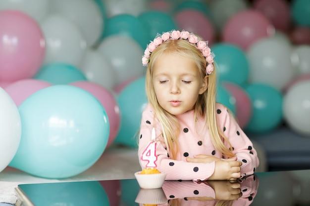 誕生日の蝋燭を吹くかわいい女の子 Premium写真
