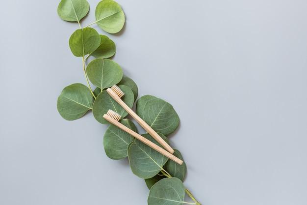 エコ天然竹歯ブラシフラット灰色の背景に置く Premium写真