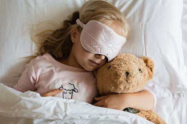 パジャマとテディベアと白いベッドで寝ている目隠しの少女 Premium写真
