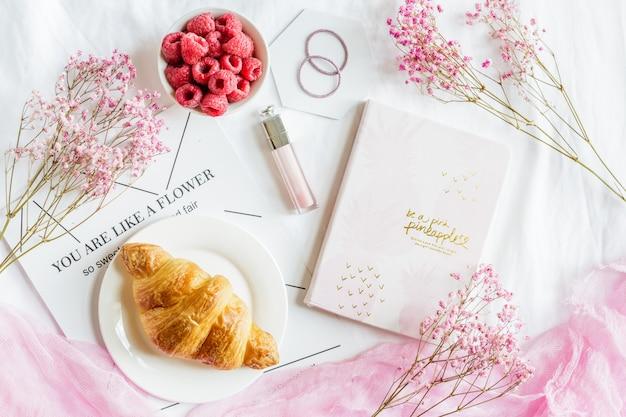 クロワッサンペストリー、新鮮なラズベリー、ノート、リップグロス、ピンクの花のシーン。 Premium写真