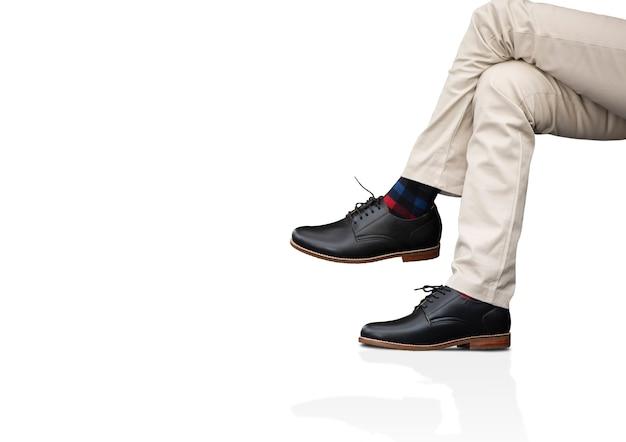 Мужчина носит длинные брюки и кожаные черные туфли для мужской коллекции одежды Premium Фотографии