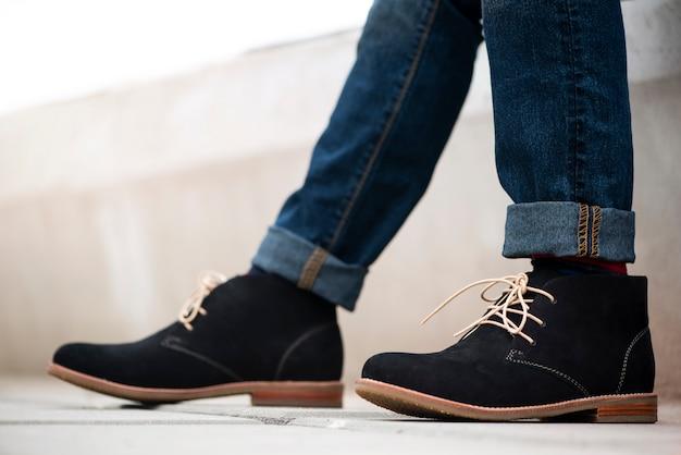 Модель одета в синие джинсы и черные ботильоны для мужской коллекции. Premium Фотографии
