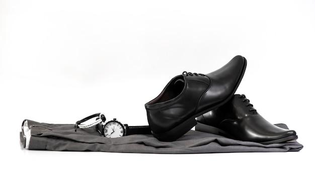 Мужская одежда с черными туфлями, часы и браслет на белом фоне Premium Фотографии