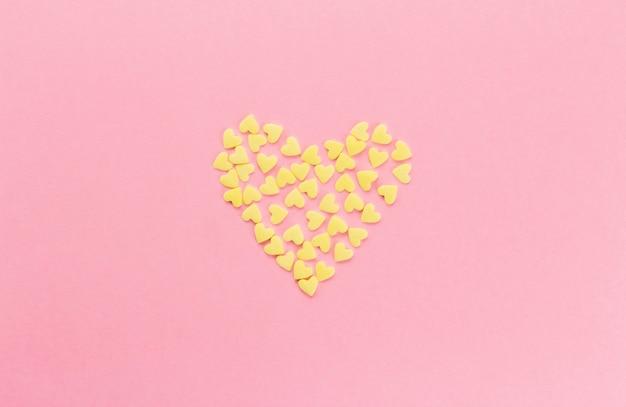 ピンクの背景のコピースペースにハートの形をした黄色の紙吹雪 Premium写真
