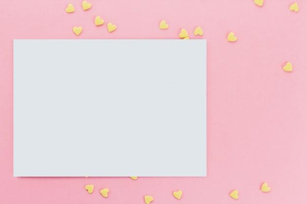 ピンクの背景のコピースペースにハート型の菓子紙吹雪の背景のカード。イエローハート Premium写真