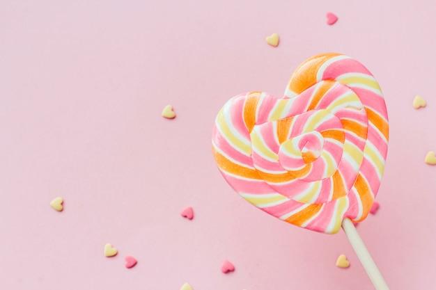 ピンクの背景のコピースペースに大きなストライプハート型ロリポップと菓子紙吹雪 Premium写真