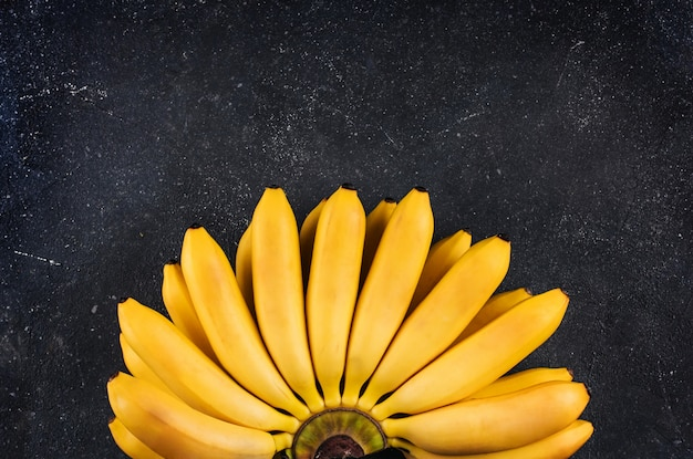 暗い灰色の大まかな背景コピースペースに小さな熟したバナナの束 Premium写真