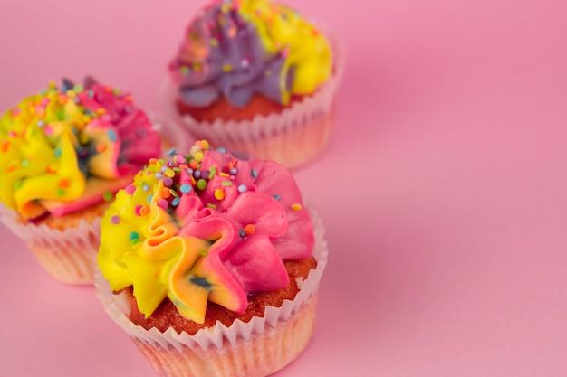 ピンクの背景のコピースペースにマルチカラーのクリームと自家製カップケーキ。黄色とピンクのクリーム。 Premium写真