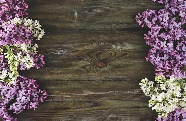 古い木製の背景にライラックの花。ライラックの花のボーダーコピースペース。 Premium写真