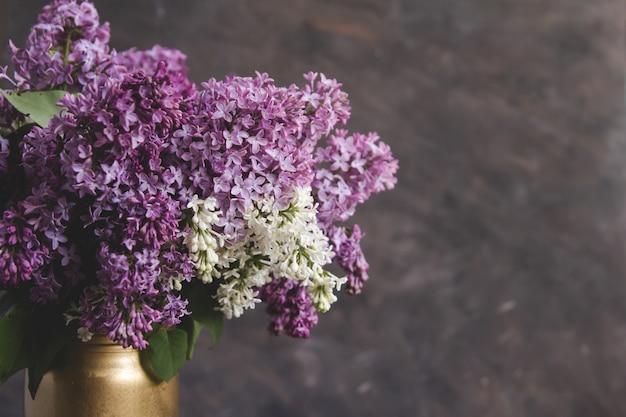 灰色の背景に金色の花瓶にライラックの花束。咲くライラック。 Premium写真