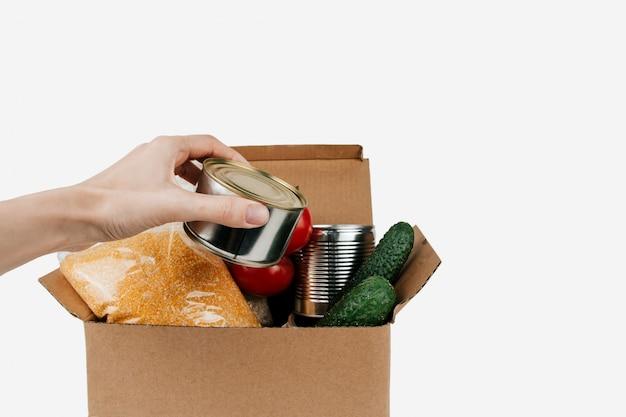 製品のボックス。分離された段ボール箱に野菜、シリアル、缶詰。手にブリキ缶。 Premium写真