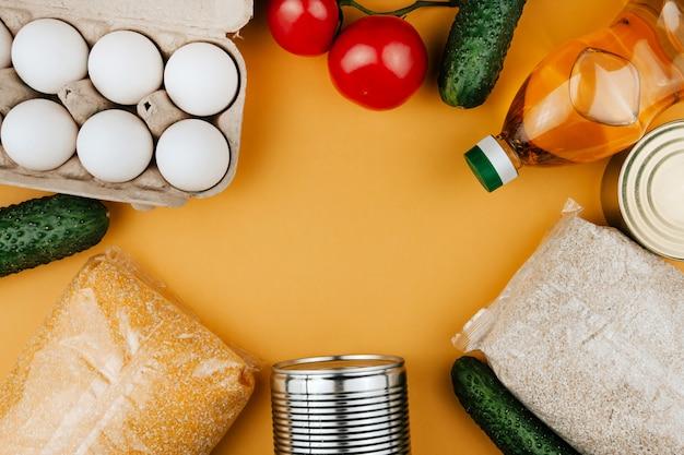 黄色の背景に寄付のための製品。野菜、シリアル、缶詰。食料の寄付はスペースをコピーします。 Premium写真
