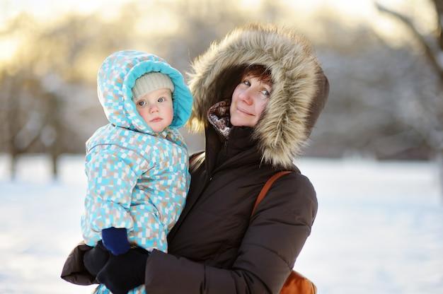 美しい中年の女性と冬の公園で彼女の愛らしい小さな孫 Premium写真