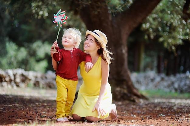 幸せな女性農家と彼女の小さなヘルパーはイタリアのオリーブ畑で働いています。 Premium写真