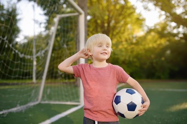 楽しんで夏の日にサッカー/フットボールの試合を楽しんでいる少年。 Premium写真