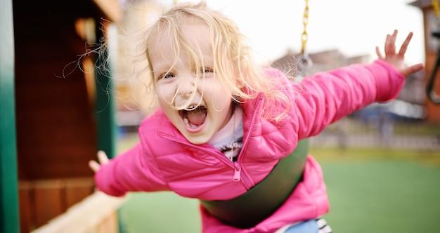 屋外の遊び場で楽しんでかわいい女の子 Premium写真