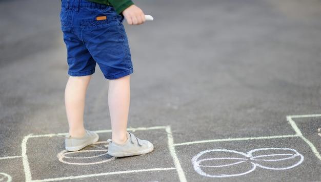 晴れた日に屋外の遊び場で石蹴りゲームを遊んでいる子供 Premium写真