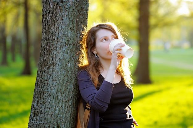 Мечтательная молодая женщина пьет кофе или чай на открытом воздухе Premium Фотографии