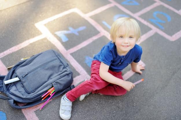 学校のコンセプトに戻る校庭の小さな男の子 Premium写真
