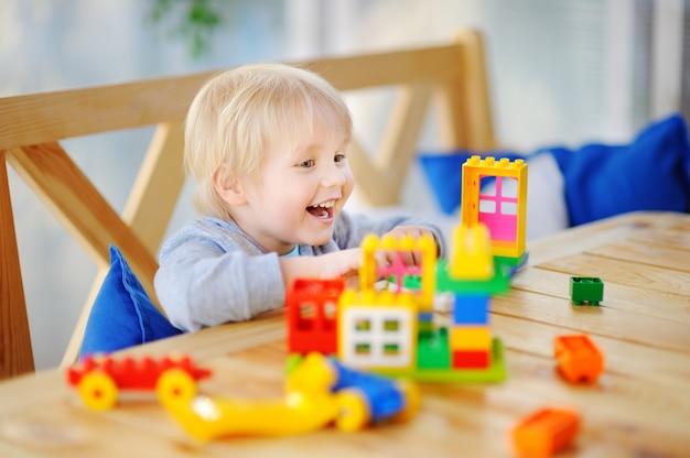 幼稚園や自宅でカラフルなプラスチック製のブロックで遊ぶ少年 Premium写真