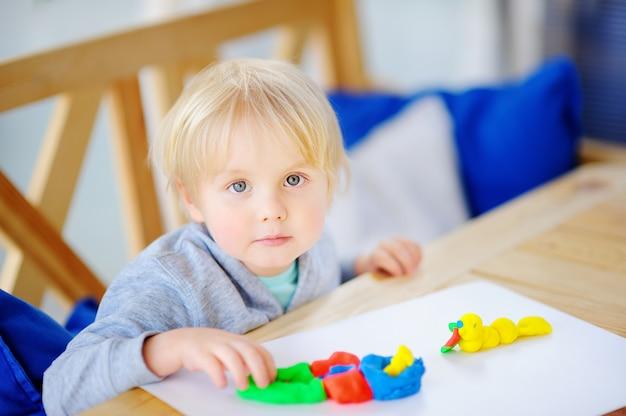 Творческий мальчик играет с красочными лепка из глины в детском саду Premium Фотографии