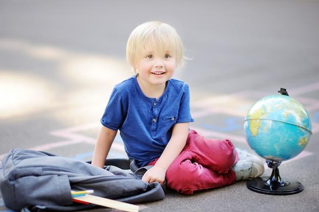 かわいい金髪の少年が近くに敷設バッグで放課後校庭の上に座って宿題をしています。 Premium写真