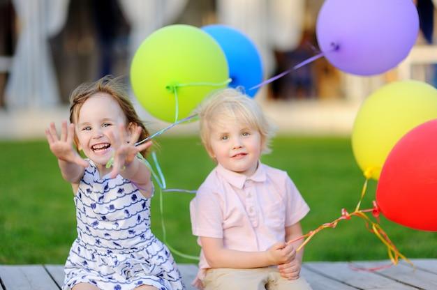 男の子と女の子が楽しんでカラフルな風船で誕生日パーティーを祝う Premium写真