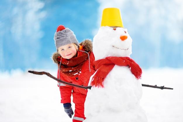 Маленький мальчик в красной зимней одежде весело со снеговиком в снежном парке Premium Фотографии