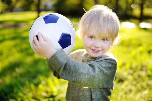 Маленький мальчик с удовольствием играет в футбол в солнечный летний день Premium Фотографии