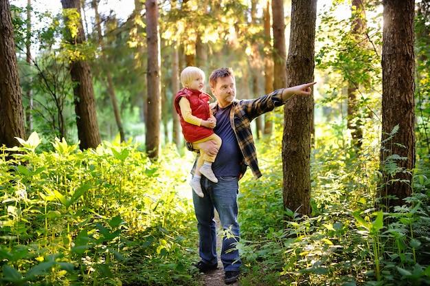 Отец и его маленький сын во время походов в лес на закате Premium Фотографии