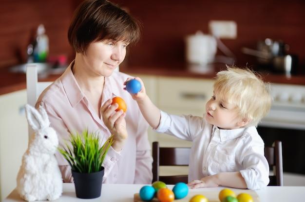 Красивая женщина и ее милый сын или внук, играя с пасхальное яйцо на пасху Premium Фотографии