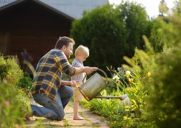 中年の男と彼の幼い息子は夏の晴れた日に庭の花に水をまく Premium写真