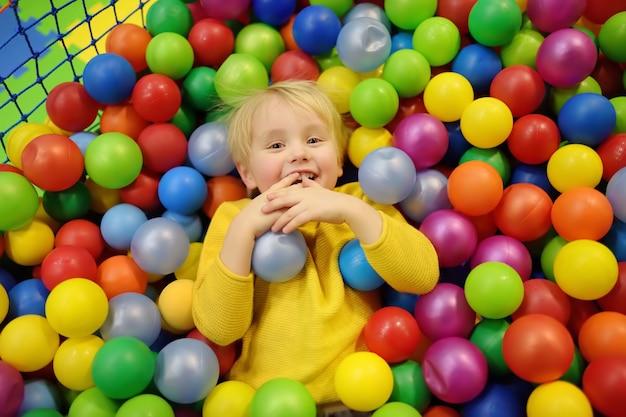 カラフルなボールとボールピットで楽しんで幸せな小さな男の子 Premium写真