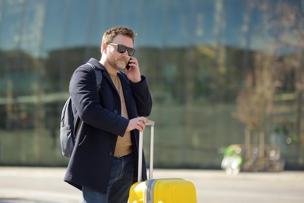 Мужчина средних лет разговаривает по телефону на центральной станции. Premium Фотографии