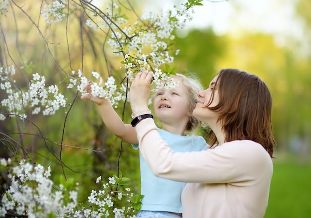 開花中に桜やリンゴの果樹園で彼女の美しい母親の腕の中でかわいい女の子。 Premium写真