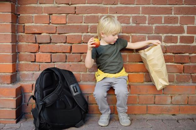 大きなバックパックとランチバッグを持った生徒が座って、校舎近くのランチを食べました。 Premium写真