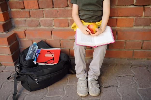 大きなバックパックとランチバッグを持った生徒は、校舎の近くで昼食を食べに座った。 Premium写真