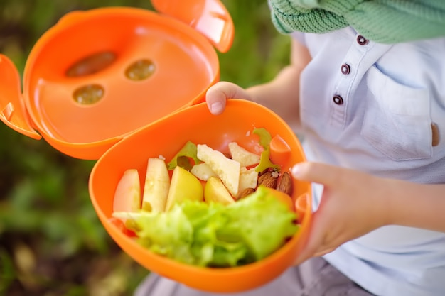 Маленький мальчик ест его обед на траве в парке на лето. Premium Фотографии