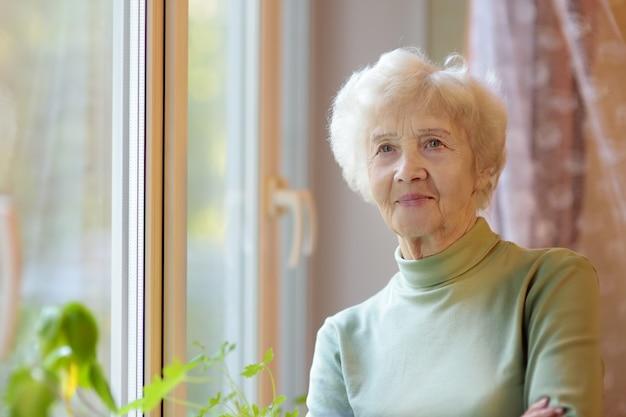 白い巻き毛の美しい笑顔の年配の女性の肖像画。老婦人は家の窓のそばに立っています。 Premium写真