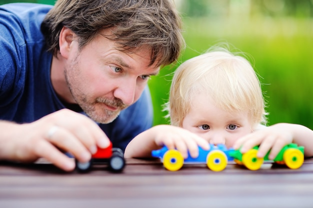 屋外のおもちゃの列車で遊ぶ彼の幼児の息子を持つ中年父親。 Premium写真