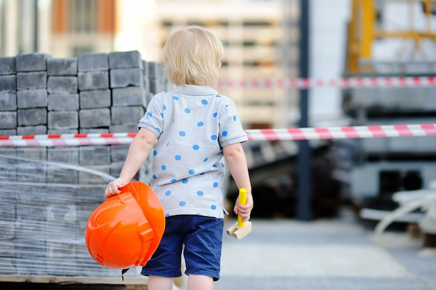 Портрет милый маленький строитель с каски и молот на открытом воздухе Premium Фотографии