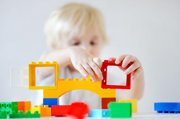 カラフルなプラスチック製のブロックを屋内で遊んでかわいい幼児男の子、手に焦点を当てる Premium写真
