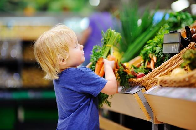 食料品店やスーパーマーケットの新鮮な有機ニンジンを選ぶかわいい幼児男の子。子供連れの若い家族のための健康的なライフスタイル Premium写真