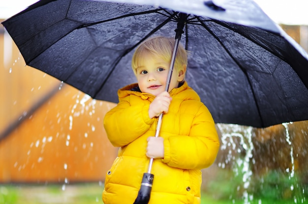 雨の曇りの秋の天気で歩く少年。雨の中で大きな黒い傘を持つ子供。秋の野外活動 Premium写真
