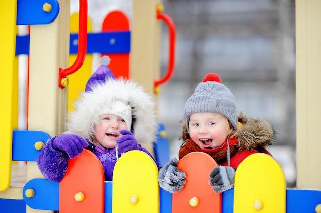 Маленький мальчик и девочка в зимней одежде веселятся на детской площадке на свежем воздухе Premium Фотографии