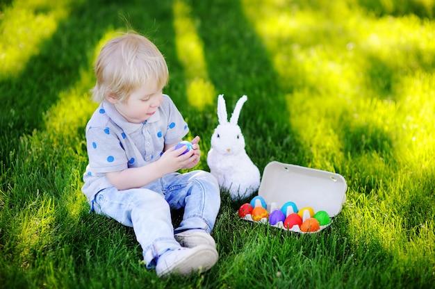イースターの日に春の庭でイースターエッグを捜す少年。ごちそうを祝う伝統的なウサギとかわいい子 Premium写真